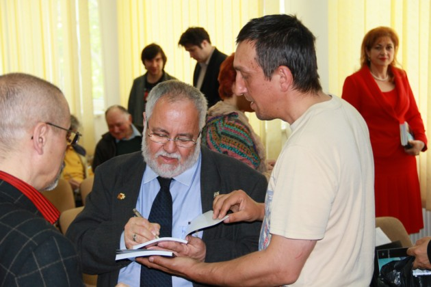 Menachem Falek scriind un autograf