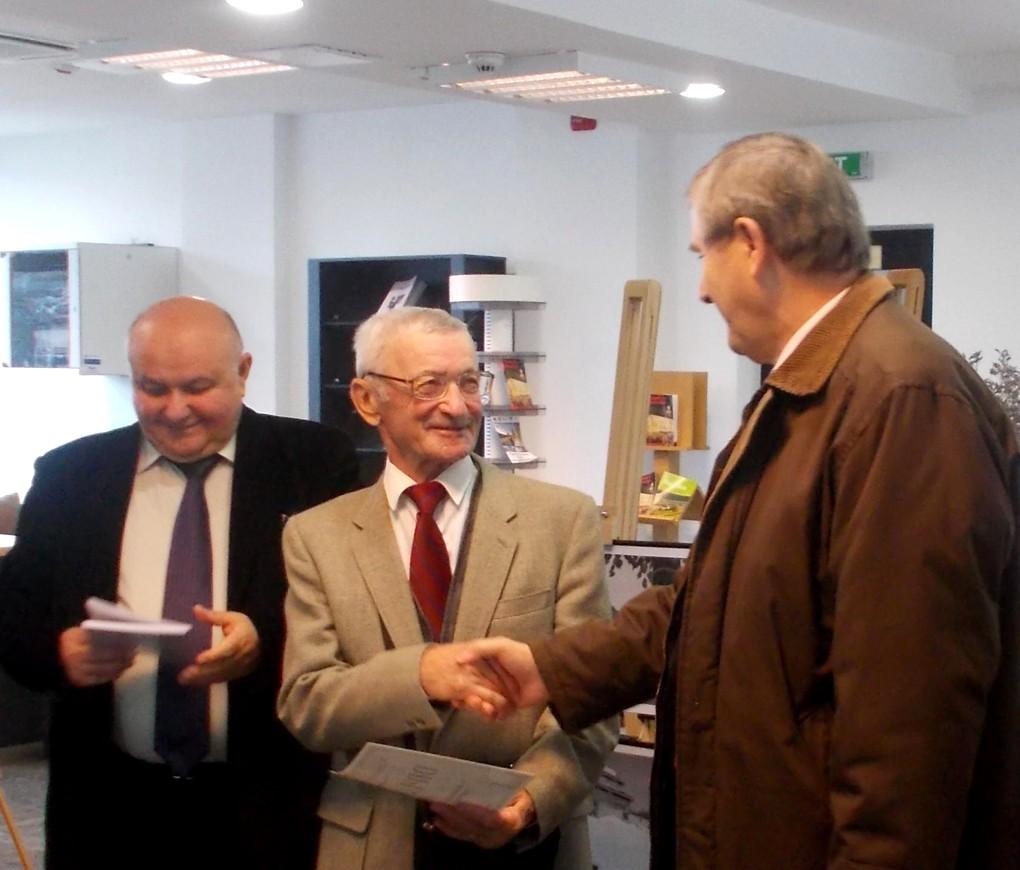 Viorel Varvaroi, înmânându-i Diploma OPERA OMNIA lui Dumitru Vinţilă, în vreme ce Dumitru Teodorescu îşi pregăteşte cuvântul de autor